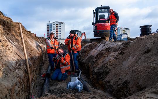 Baustelle mit Bagger und Bauarbeitern